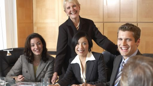 Businessmen and women at conference table in meeting, smiling